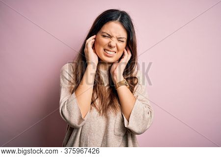 Young beautiful brunette woman wearing casual sweater standing over pink background covering ears with fingers with annoyed expression for the noise of loud music. Deaf concept.