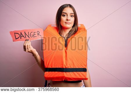 Young beautiful brunette woman wearing lifejacket holding paper with danger message with a confident expression on smart face thinking serious