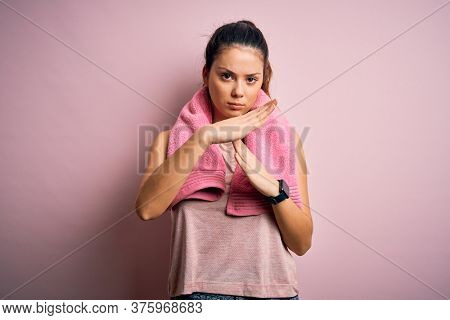 Young beautiful brunette sportswoman wearing sportswear and towel over pink background Doing time out gesture with hands, frustrated and serious face