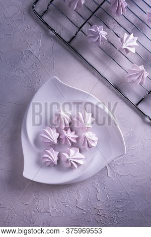 Still Life With Few Delicate Pink Meringue Cookies On White Porcelain Triangle Plate And On Metal Gr