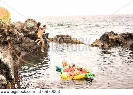 Crazy Friends Vacationers Jumping On Natural Pool At Travel Beach Location - Young People Having Fun