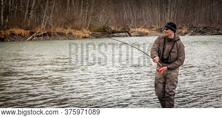 Kalum River, British Columbia, Canada - April 11th, 2017: A Fly Fisherman Hooked Into A Big Fish On