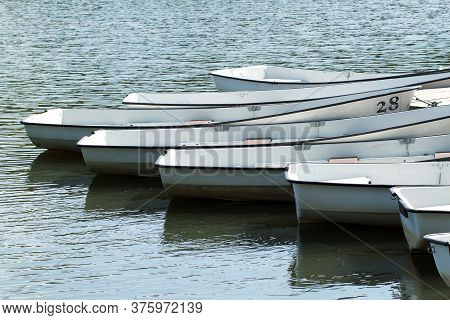 Several Boats At Pier On A Summer River Or Pond
