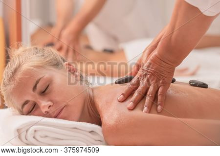 A Relaxed Looking Woman Lying Down With Black Stones On Her Back And Receiving A Massage From Two Ha