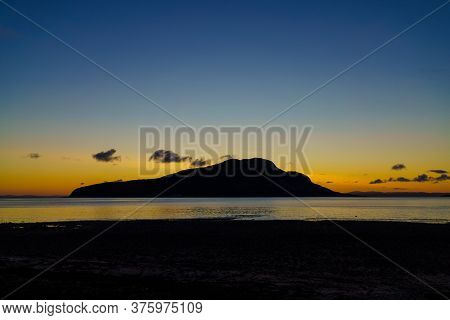 Sunrise Over Holy Isle From Lamlash Beach On The Isle Of Arran In Scotland.
