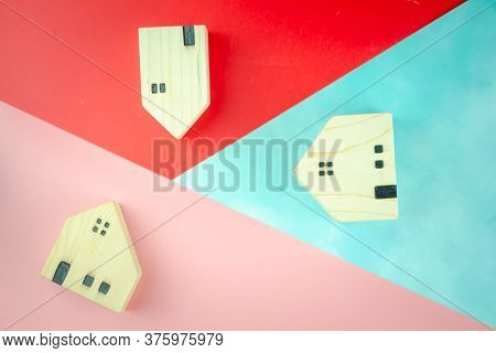 Miniature Wooden Toy House On Colorful Trendy Geometric Background. Flat Lay Top View. Simple Design