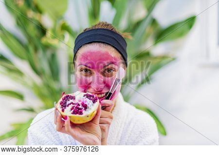 Close Up Of A Young Woman With Cream Applied On Her Face Holding An Open Pomegranate And A Makeup Br