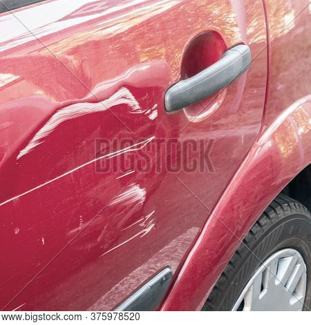 Scratched And Dented Car. Collision Or Accident. Scratches On The Side Door Of The Red Car.