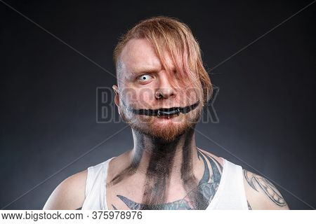Portrait Of A Tattooed Scary Mad With Horror Make-up
