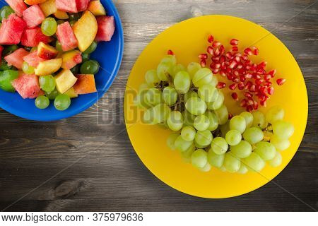 Grapes, Pomegranate On A Black Wooden Background. Grapes, Pomegranate On A Yellow Plate Top View