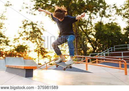 Young Cool Skater In Black T-shirt And Jeans Practicing Jumping Tricks On Skateboard At Modern Skate