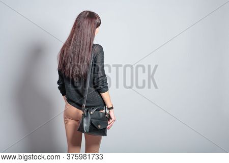 Brown Haired Woman Is Posing On Gray Background With Handbag On Her Shoulder