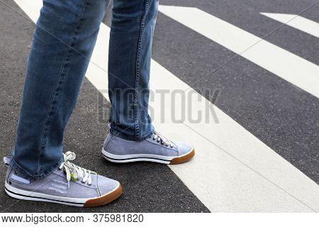 Man Crossing The Street, Female Legs In Sneakers On Pedestrian Crossing. Concept Of Road Safety. Dan