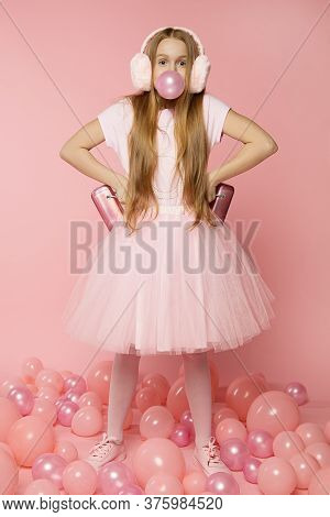 Beautiful Fun Girl In Clothes On Pink Background With Balloons And Accessories. Pout Chewing Gum Wit