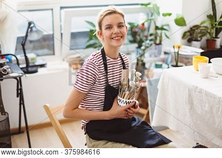 Cheerful Girl In Black Apron And Striped T-shirt Holding Bowl With Pottery Tools In Hands Happily Lo