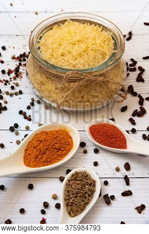Ingredients For Cooking Pilaf: Rice In A Glass Jar In The Background, Garlic, Cumin, Saffron And Pap