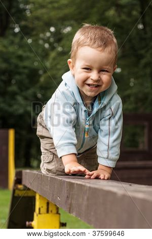 Happy Young Boy Crawling On The Ladder