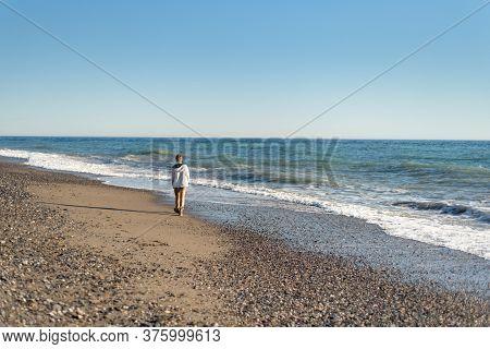 Young Teen Boy Walking Along Shoreline Of Beach