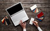 Laptop with color swatches with woman's hands holding pencil on old wooden table. Workplace designer. poster