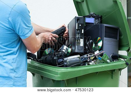 Man discarding old electronics int the plastic bin poster
