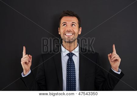 Businessman pointing up on copy space
