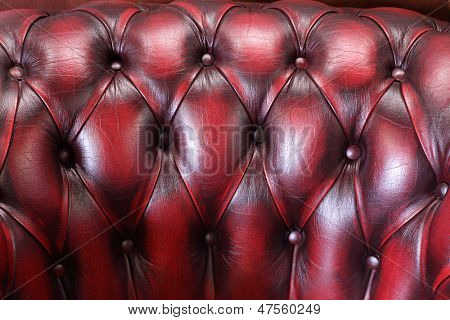 Backrest of soft red luxury leather armchair for relaxation.