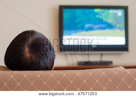a woman sit on sofa is watching TV