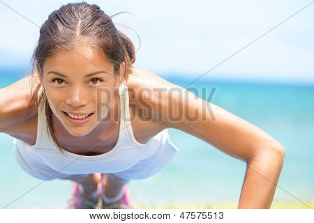 Sport fitness woman training push-ups. Female athlete exercising push up outside in sunny sunshine. Fit girl fitness model in exercise outdoors. Healthy lifestyle concept.