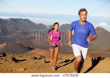 Running sport - trail runners in cross country run. Man and woman couple athletes training in amazing nature landscape. Fit male fitness model and female athlete working out facing challenges.