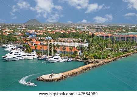 a speedboat steers around a helipad in a marina in Aruba poster