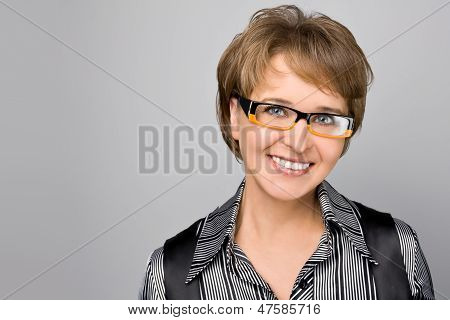 Portrait Of The Business Woman In Glasses On A Grey Background