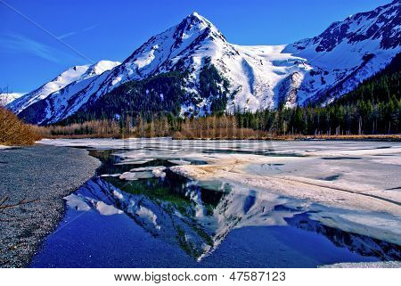 Partially Frozen Lake with Mountain Range Reflected in the Great Alaskan Wilderness.  A Beautiful Landscape of Blue Sky, Trees, Rock, Snow, Water and Ice.  Near Seward highway near Anchorage, Alaska. poster