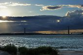 Sunbeams coming through the clouds at sunset time on Hudson river with Verrazano bridge on background poster