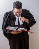 Man in canadian lawyer toga holding a book of law laughing at it poster