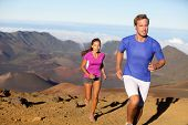 Running sport - trail runners in cross country run. Man and woman couple athletes training in amazing nature landscape. Fit male fitness model and female athlete working out facing challenges. poster