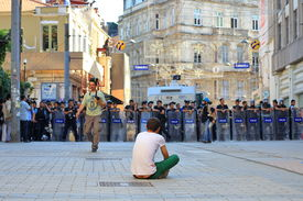 Man sitting down in front of police line