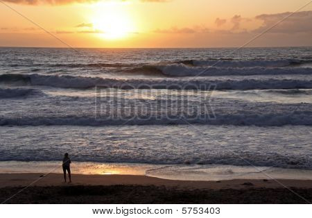 A silhouetted lady watching the sun set, land / sea scape at the famous surfing beach Fistral Bay, C