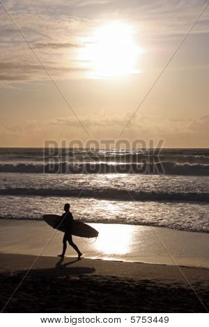 Silhouette of a surfer with surf board walking along the water line at the famous surfing beach Fist