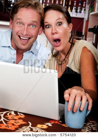 Attractive couple in a coffee house with laptop computer poster