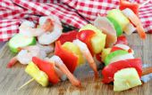 Shrimp chicken red peppers and pineapple cubes on skewers ready to grill. poster