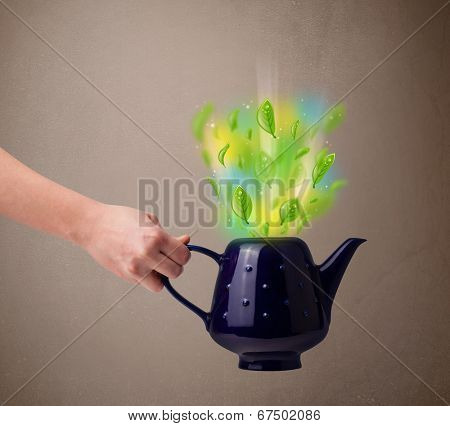 Tea pot with leaves and colorful abstract lights, close up