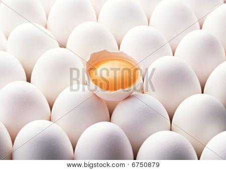 One solitary broken egg among other fresh unbroken eggs.