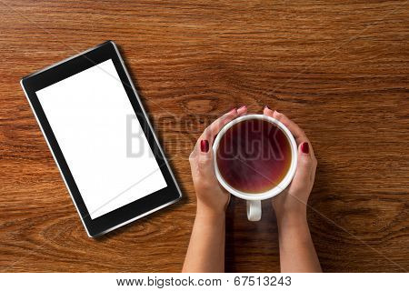 woman holding hot cup of tea with tablet pc on wooden table