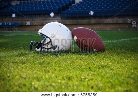 A football helmet  and ball rest on the field in a stadium. Copy space below poster