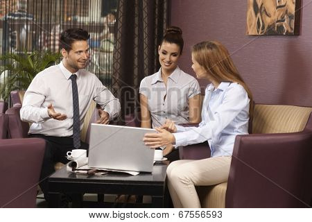 Young businessteam working with laptop in coffee bar.