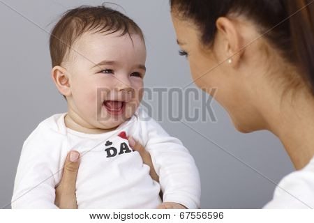 Happy baby boy laughing in mother's arms.