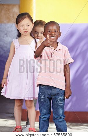 Happy african child in kindergarten group holding his thumbs up