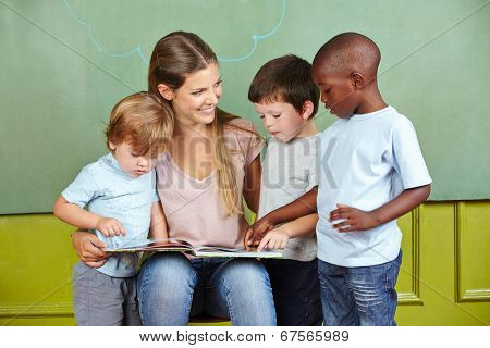 Happy child day care worker with children reading a book in kindergarten