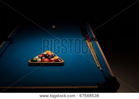 Pool balls stacked in the triangular rack, the cue ball and cues on a blue baize table in a shadowy dark nightclub waiting for the next players