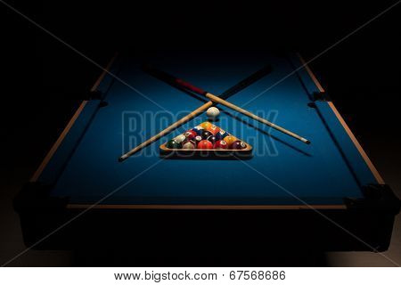 Pool equipment ready for a game with crossed wooden cues, racked balls and a cue ball on a blue baize table surrounded by darkness